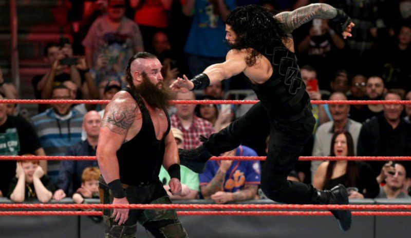 Roman Reigns on the verge of hitting Strowman with a spear