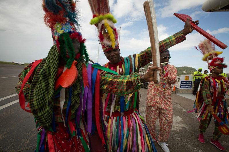 Masquerade dancers with the Baton to St Kitts and Nevis