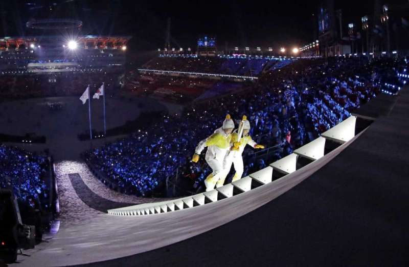 North Korea's Jong Su Hyon, left, and South Korea's Park Jong-ah carry the torch during the opening ceremony of the 2018 Winter Olympics