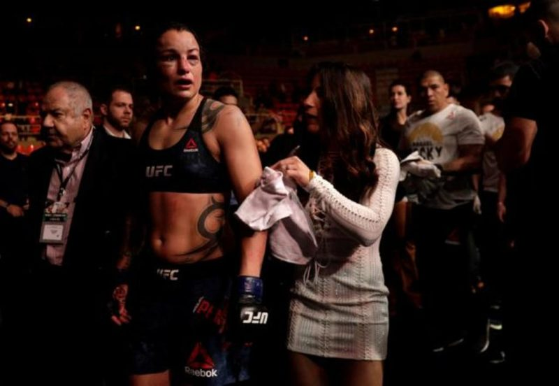 Raquel Pennington leaves the cage with her fiancee Tecia Torres