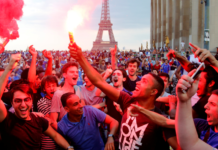 France fans let off flares as they celebrate in front of the Eiffel Tower.