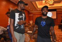 Kevin Durant, left, and Kyrie Irving talk during a team meeting