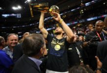 Stephen Curry hoists the Larry O'Brien trophy