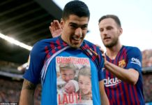 Suarez of Barcelona celebrates scoring a second goal by revealing a picture of his new child