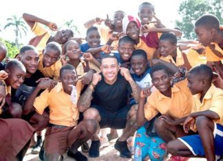 Memphis Depay (squatting) surrounded by some students of the Cape Coast School for the Deaf and the Blind.