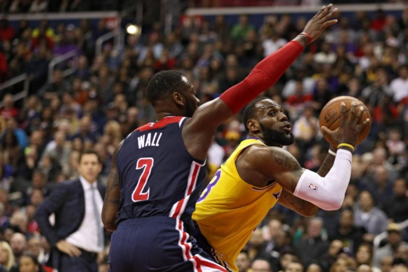 LeBron James of the Lakers is defended by John Wall of the Washington Wizards