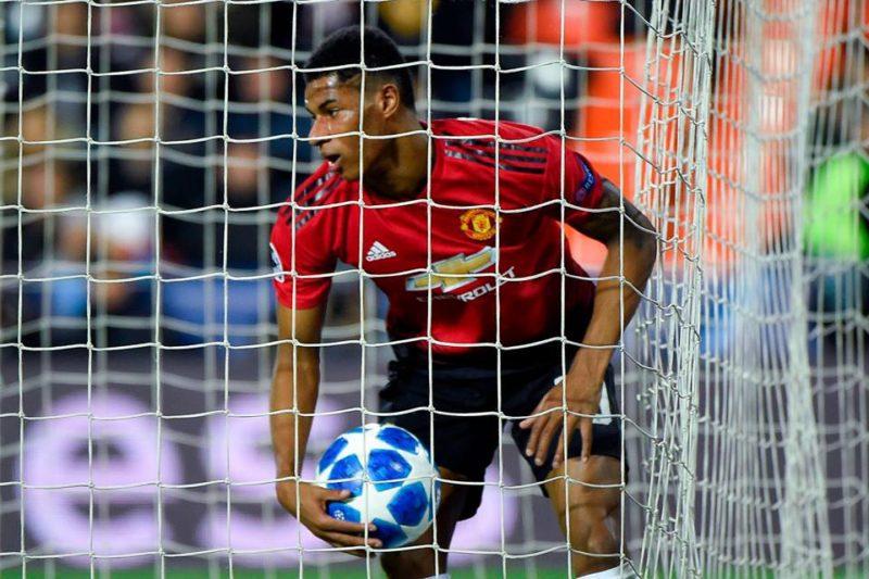 Marcus Rashford picks the ball from the net